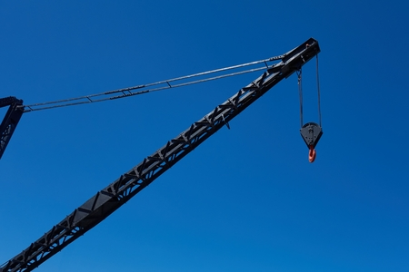 polea: Black crane arm with red hook on blue sky background.