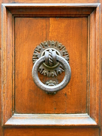 An old door knocker at the historic door of a European city.