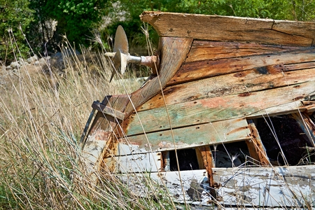 Wreck of a small boat with a rusty ship screw. Banque d'images