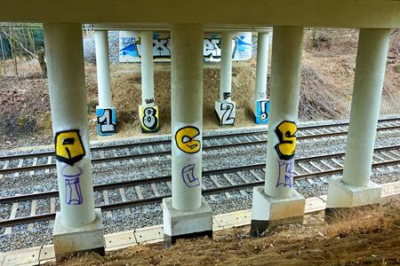Vandal graffiti on support pillars crossing over a railway track.