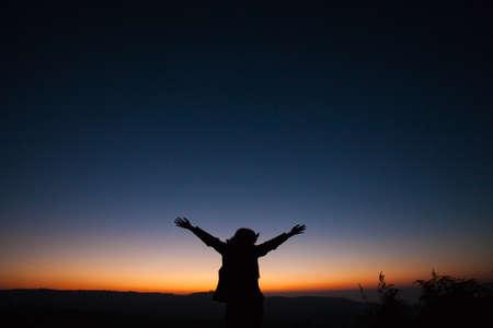 reveille: a women hug the sky after sunset Stock Photo