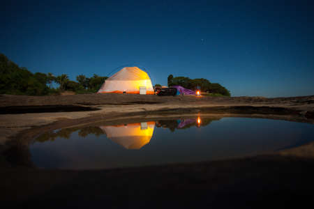 women sleep front of tent under starlight