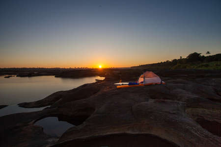 campsite: man sit front of camping tent glow up with sunrise in morning