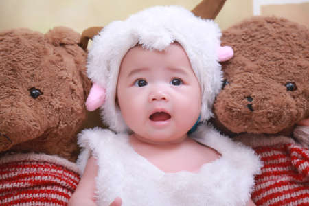 babygirl: Cute little girls wearing sheep sits in the middle of a teddy bear