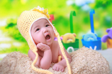 babygirl: Cute little girl lying on the blanket with face propped on hand