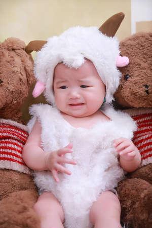 babygirl: Cute little girl wearing sheeps coat sat in the little bear