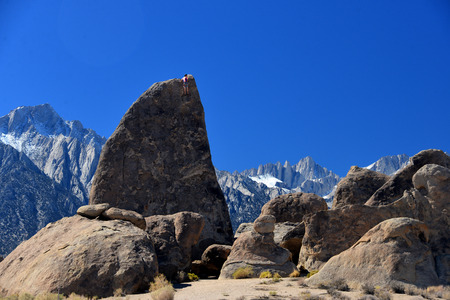 alabama hills: climber on sharks fin arete route with mount whitney in back ground at alabama hills , california