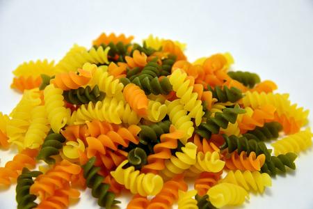 rotini: Tri colored rotini pasta on a white background