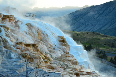 minerva: Geothermal flow of hot, carbonate rich water, forms cascading, dark orange travertine terraces, with steam rising and mountains in the background, at Mammoth Hot Springs in Yellowstone, Wyoming Stock Photo