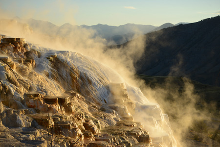 hot water geothermal: Geothermal flow of hot, carbonate rich water, forms cascading, dark orange travertine terraces, with steam rising and mountains in the background, at Mammoth Hot Springs in Yellowstone, Wyoming Stock Photo