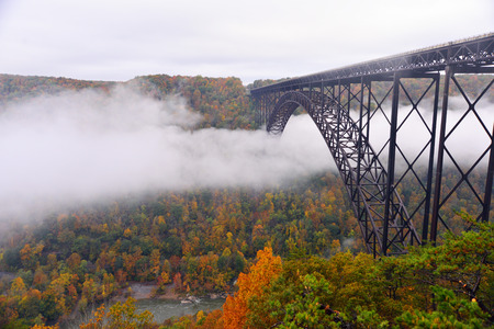 Fog in the morning going under the New River Gorge Bridge Stock Photo