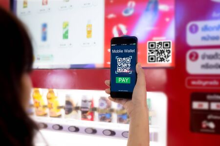 Mobile wallet concept.Woman hands scaning QR code via mobile phone with Smart Vending machine as background