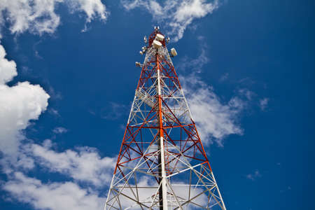 Red and white tower of communications with with a lot of different antennas under clear sky   photo