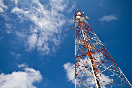 Red and white tower of communications with with a lot of different antennas under clear sky