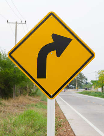 Curved Road Traffic Sign on the road at country side photo