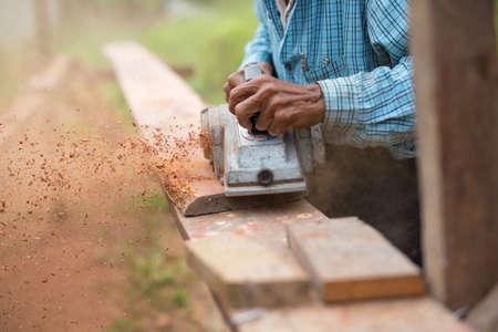 planos electricos: carpintero usando cepillo eléctrico con tablón de madera en el taller de carpintería