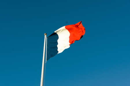 French flag on a sunny autumn day against a blue sky photo