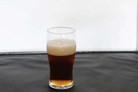 one glass of coold and dark beer ready to drink photo