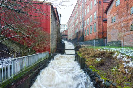rushing water: rushing water rushing down from a factory of many building Stock Photo
