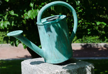 wateringcan: one old watering can on a stone beutiful decoration