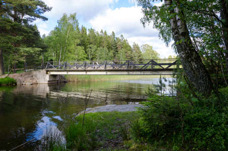 scandinavian landscape: beutiful swedish natur with a lake and one bridge and clouds on the sky