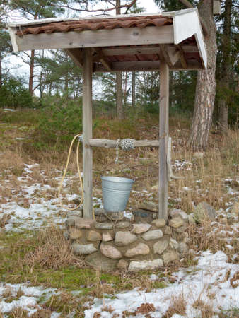 well made: one old well in the forrest with a chain and a water range Stock Photo