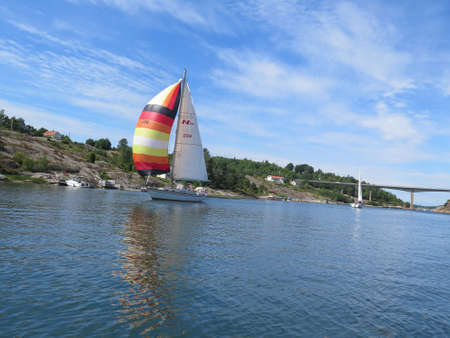 sailing boats: one sailboat on sweden westcoast just pass a bridge