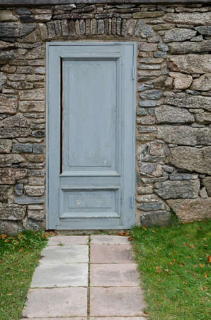 gunnebo: one old and grey door in the stone wall at Gunnebo castle