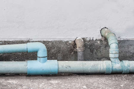 waste water: old waste water pipe on wall background