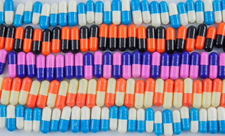 antibiotic pink pill: variety of pill capsules on white background, colorful