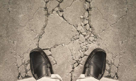 investment risk: a man standing on crack ground, for risk concept
