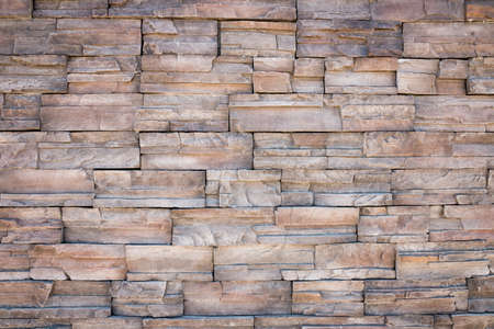 earth tone: old wall stone tiles background with earth tone