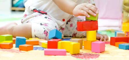 baby playing a wood block toys, tried to building Stockfoto