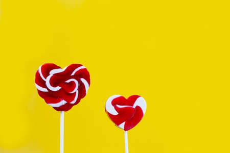 candy stick: colorful candy stick heart shape on yellow background