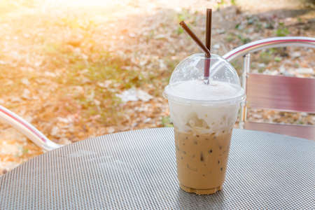 capuchino: plastic glass of iced coffee capuchino on metal table with sun light above