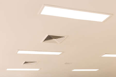 exhaust fan: ceiling and fluorescent lighting with exhaust fan louver, selective focus Stock Photo