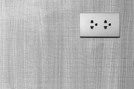 dual electric outlet with ground, neutron, on wood wall, black and white tone