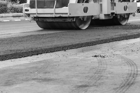 road roller repairing concrete road, asphaltic topping, black and white tone