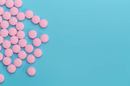 pink pills on blue background, medical and health care concept