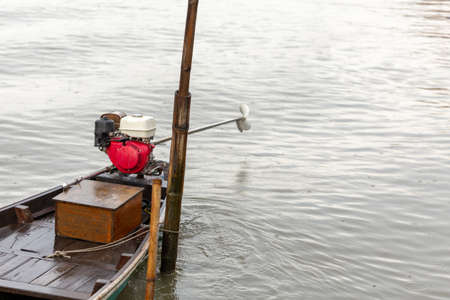 old wood boat with motors on water in raining day