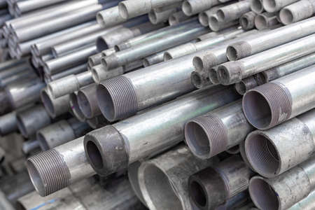 stack of steel electric conduit pipes, black and white tone, selective focus, industry concept background