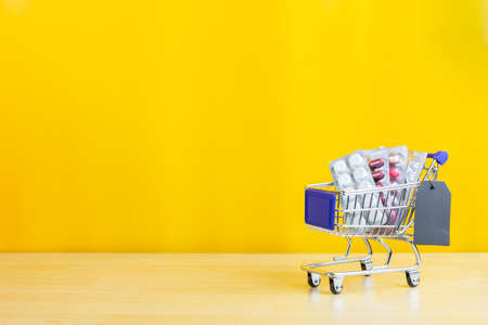 pills and drugs on shopping cart on wood table and yellow background, medical and health care concept Stock fotó