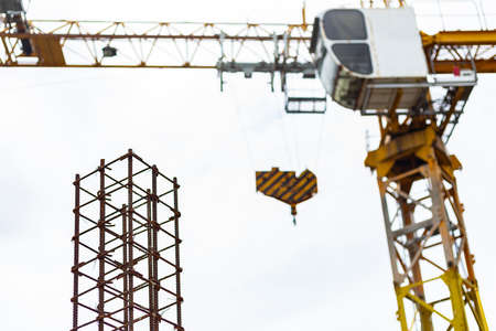 rusty steel reinforcement with tower crane background, industry construction concept