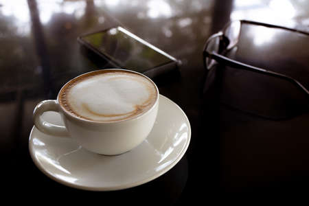 white cup of latte coffee on black table and smart phone, glass ware background, business morning concept, selective focus