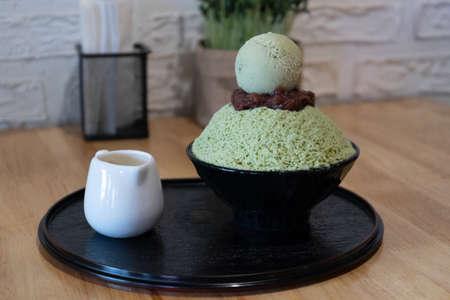Closeup green tea Bingsu on tray, Bingsu or Bingsoo, Korean shaved ice dessert with sweet toppings and fruit and varieties with ingredients, popular dessert.