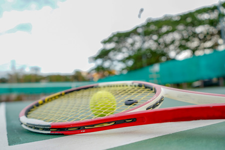 tennis ball and racket on hard court