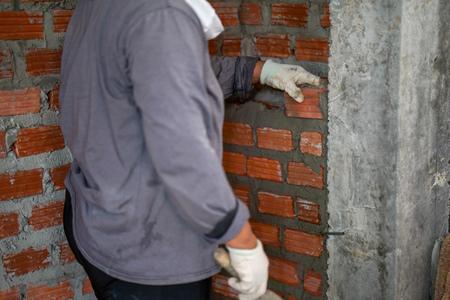 Close up of industrial bricklayer installing bricks on construction site in thailand Standard-Bild - 107320599