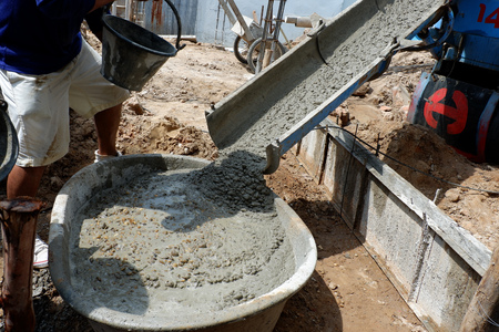 Worker leveling concrete poured from mixer on construction site Standard-Bild - 107327205