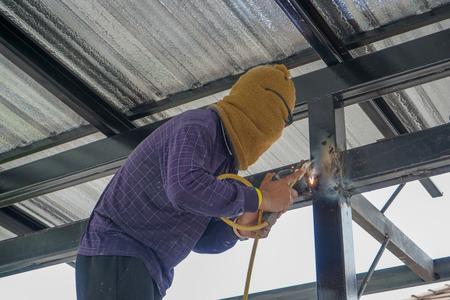 Welders are welding steel roof frame of home Standard-Bild - 107327207