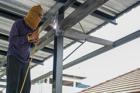 Welders are welding steel roof frame of home